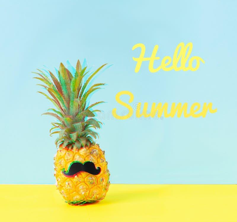 Geklede omhoog vrolijke ananas met een zwarte snor en de uitdrukkings hello zomer een blauwe gele achtergrond Glitch effect stock foto