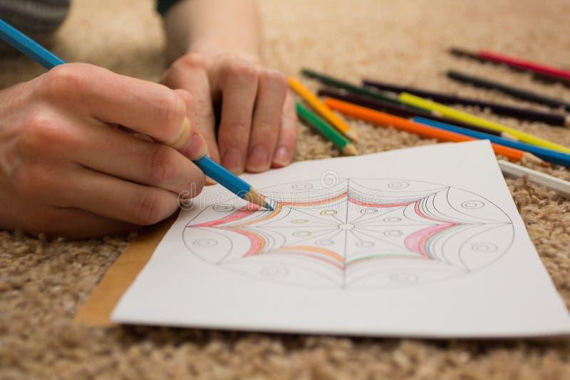 Gekleurd - antistress met blauw potlood Het meisje trekt op het tapijt royalty-vrije stock foto's