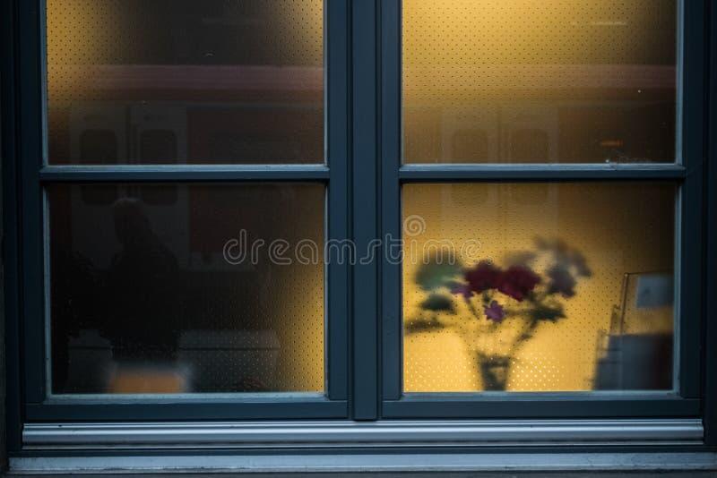 Gekleurd blauw venster met bloemen achter het glas stock afbeeldingen