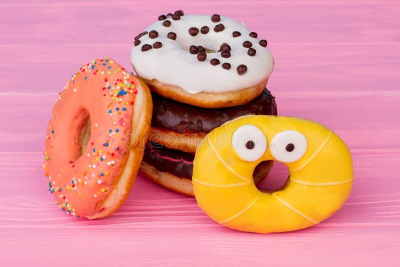 Gekleurd donuts op roze houten achtergrond stock afbeelding