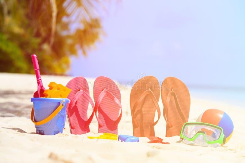 Gekleurd pantoffels, speelgoed en het duiken masker bij strand royalty-vrije stock afbeelding