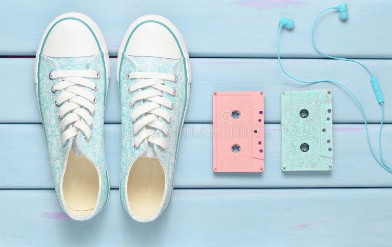 Gekleurde audiocassettes, hoofdtelefoons, tennisschoenenschoenen op een purpere pastelkleurachtergrond Ouderwetse technologieën H stock afbeeldingen