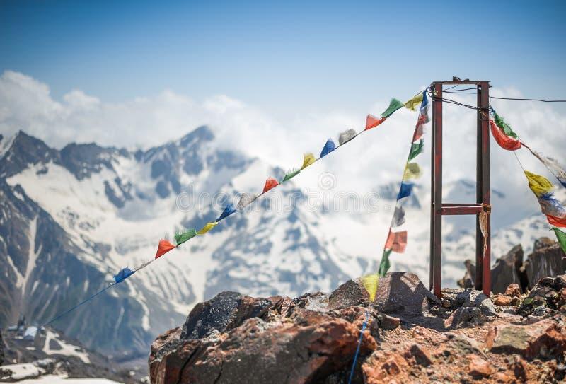 Gekleurde Boeddhistische vlaggen met mantras dichtbij de basis van klimmers op Onderstel Elbrus bij een hoogte van 3800 m stock afbeelding