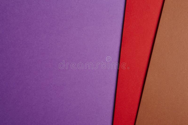 Gekleurde carboardsachtergrond in purpere, rode, bruine toon Exemplaar SP royalty-vrije stock afbeelding