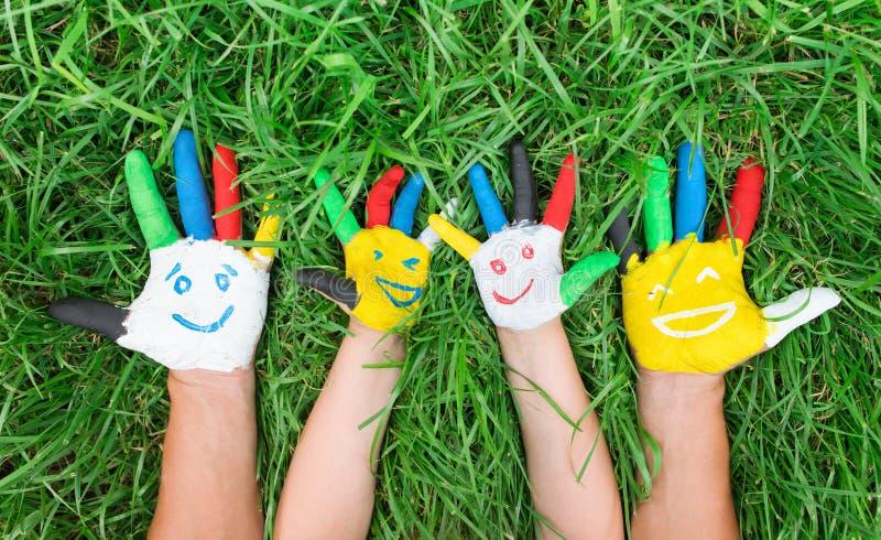 Gekleurde die handen met glimlach in kleurrijke verven tegen gree worden geschilderd stock foto