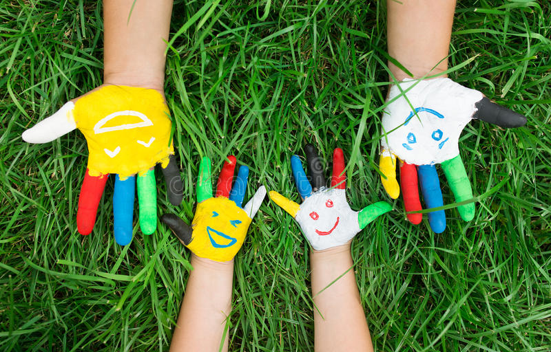 Gekleurde die handen met glimlach in kleurrijke verven tegen gree worden geschilderd royalty-vrije stock afbeeldingen