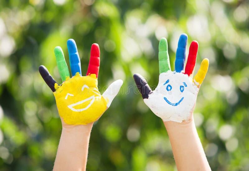 Gekleurde die handen met glimlach in kleurrijke verven worden geschilderd stock fotografie