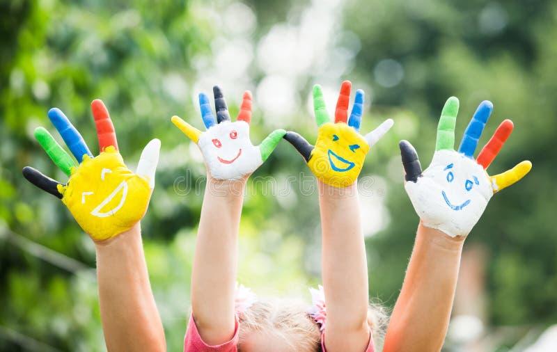 Gekleurde die handen met glimlach in kleurrijke verven worden geschilderd royalty-vrije stock foto's