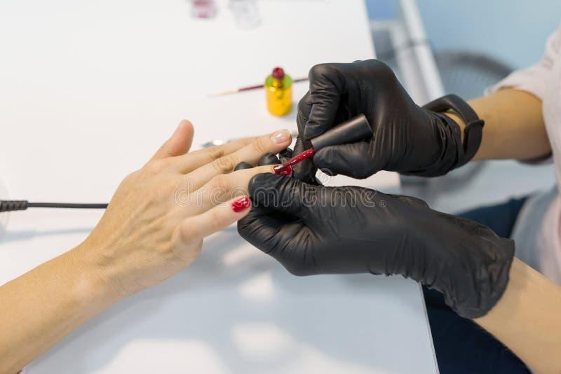 Gekleurde manicure, spijker het schilderen Vrouwenmanicure die professionele manicure doen, die het poetsmiddel van het kleurenge royalty-vrije stock foto