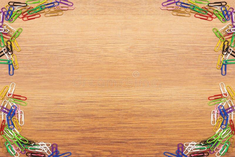 Gekleurde paperclippen op een houten achtergrond royalty-vrije stock afbeeldingen