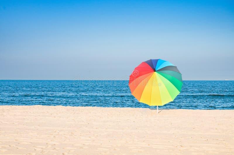Gekleurde paraplu op strand met wit zand en blauwe hemel stock afbeeldingen