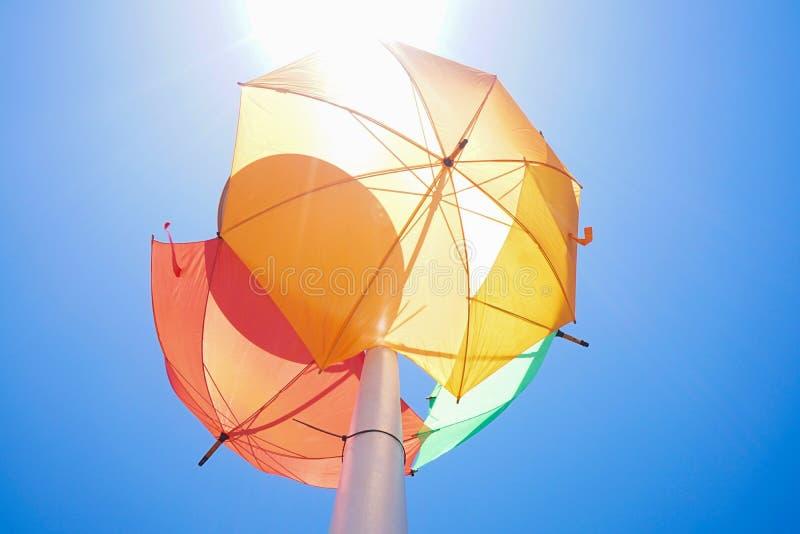 Gekleurde paraplu's op straatlantaarn tegen blauwe hemel stock foto's