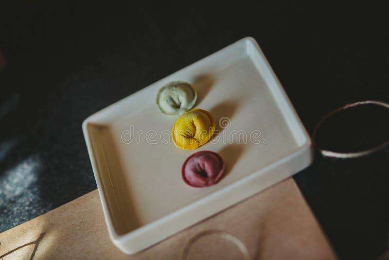 Gekleurde ravioli op de witte plaat stock fotografie