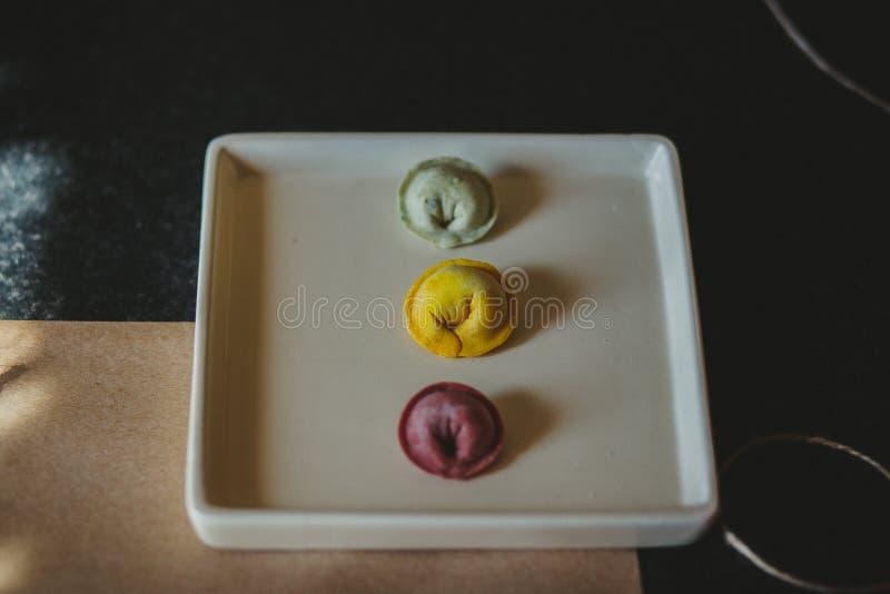 Gekleurde ravioli op de witte plaat stock afbeeldingen