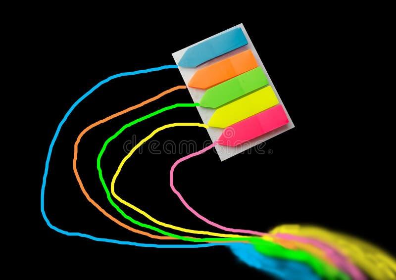 gekleurde referenties die aan een notitieboekje of een boek in bijlage die zijn, op een zwarte achtergrond wordt geïsoleerd stock afbeeldingen