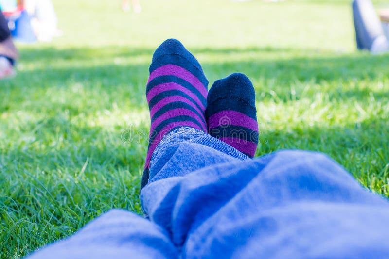 Gekleurde sokken van een tiener die in een park rust royalty-vrije stock afbeelding
