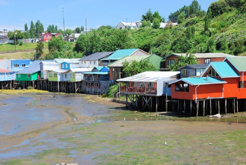 Gekleurde stelthuizen Castro tijdens eb, Chiloe-Eiland, Chili stock foto