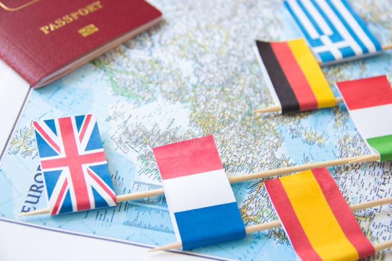 Gekleurde vlaggen van Europese landen en buitenlands paspoort op een kaart: Frankrijk, Italië, Engeland het UK, Spanje, Griekenla stock foto's