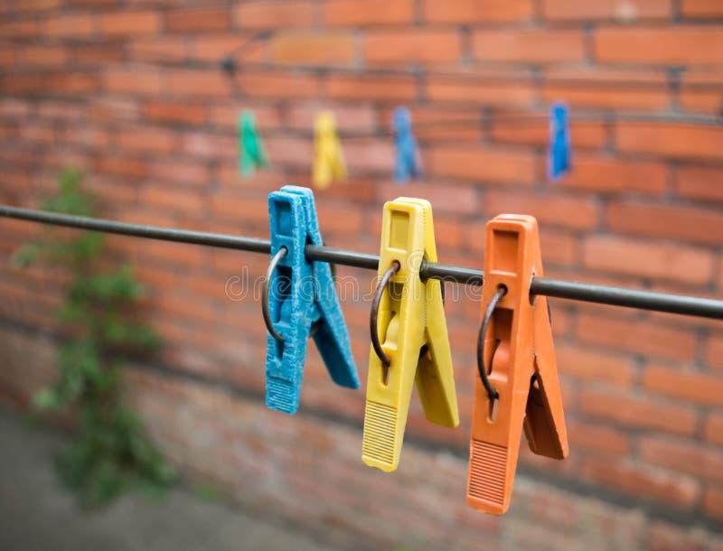 Gekleurde wasknijpers aan de draad stock fotografie