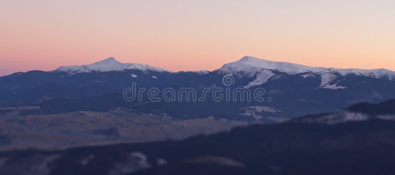 Gekleurde zonsondergang in bergen met twee pieken stock foto