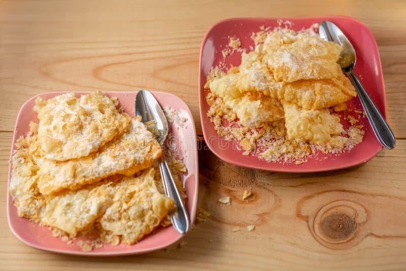 Geknapperde knapperige koekjes met gepoederde suiker Smakelijk zoet koekjeskreupelhout op een roze plaat en theelepeltjes stock afbeeldingen