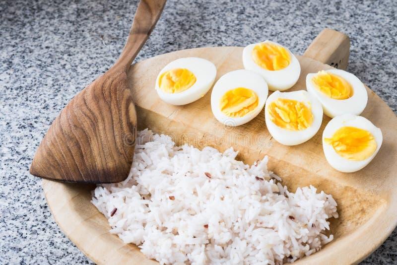 Gekochte Eier mit Reis in der hölzernen Platte lizenzfreie stockfotos