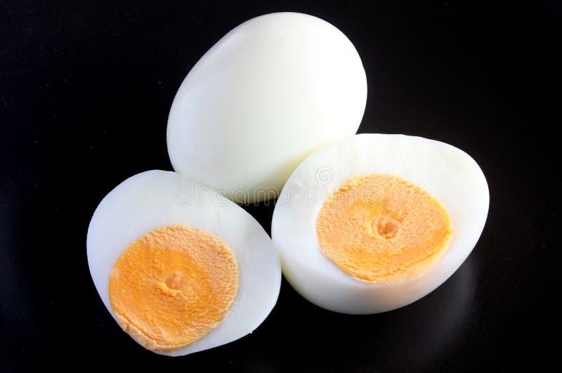 Gekochte Eier und Hälfte auf einem schwarzen Hintergrund stockbilder