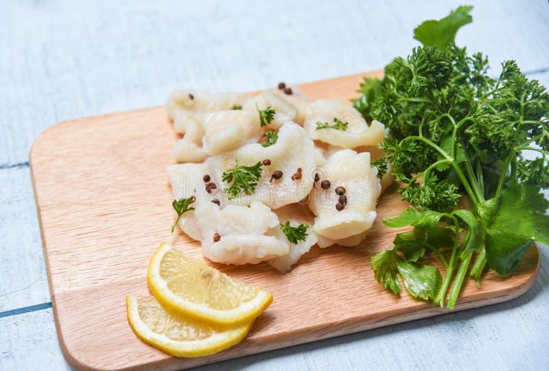 Gekochte Fischfilet Stück mit Zitrone und Gewürzen auf hölzernem Schneidebretthintergrund - pangasius Transportwagen-Fischfleisch lizenzfreies stockfoto