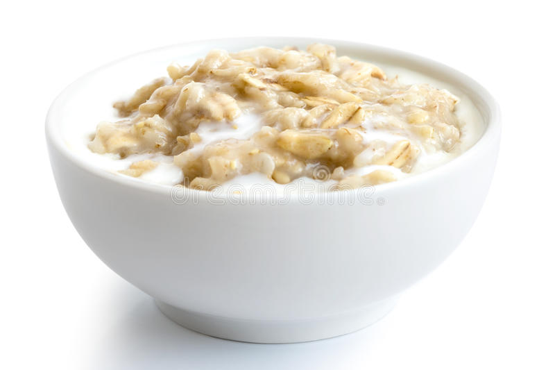 Gekochte ganze Breihafer mit Milch in weißem keramischem Schüssel isola lizenzfreies stockfoto