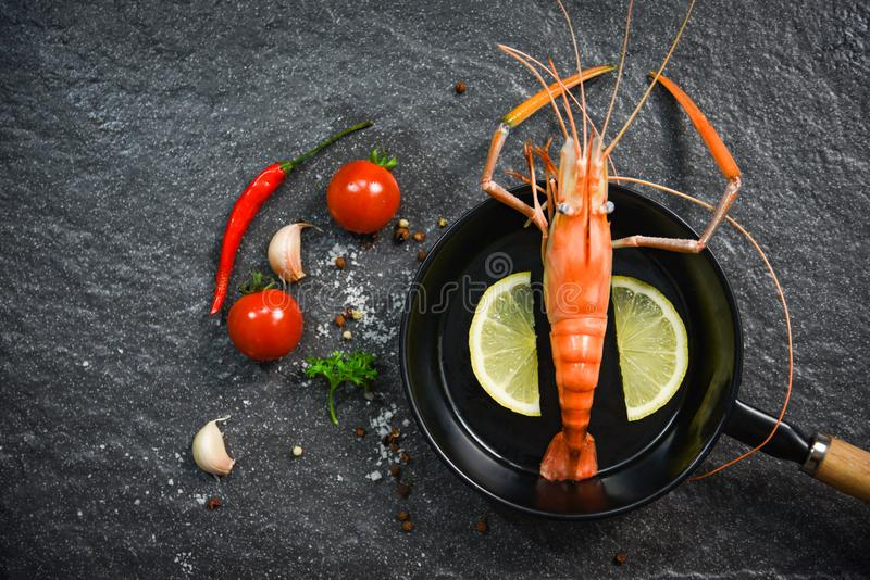 Gekochte heiße Wanne der Garnelengarnelen Meeresfrüchte mit Zitronenkräutern und -gewürz auf dunklem Hintergrund stockfotos