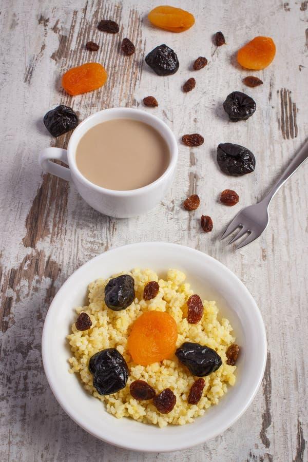 Gekochte Hirsegrützen auf weißer Platte und Tasse Kaffee mit Milch, gesundem Lebensmittel und Nahrung lizenzfreie stockbilder