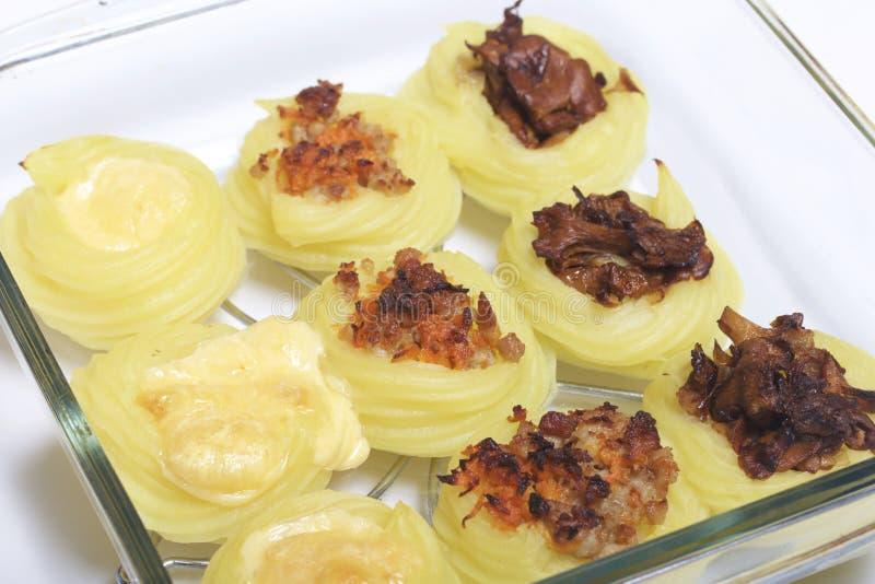 Gekochte Kartoffelkroketten angefüllt mit Käse, Pilzen und Hackfleisch Sie legen in ein Glasbackblech Die Bestandteile sind einge lizenzfreies stockbild