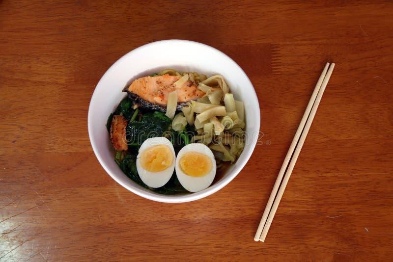Gekochte sofortige Nudeln mit gekochtem Ei, Fischfleisch, grünen Blattgemüsen und Essiggurkenkopfsalat in der weißen Schüssel lizenzfreie stockfotografie