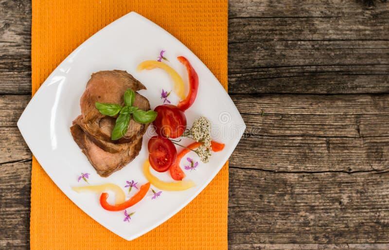 Gekochter geschnittener Hackbraten mit Tomate, Pfeffer und Basilikum Hölzerner Hintergrund Nahaufnahme stockbild