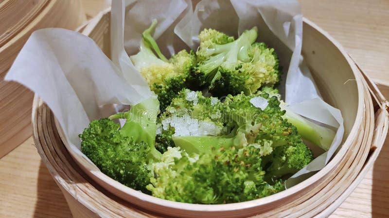 Gekochter grüner Brokkoli mit grobem Salz in einem hölzernen Behälter lizenzfreies stockbild