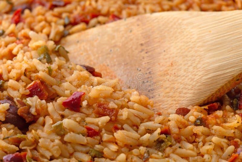 Gekochter mexikanischer Reis und Bohnen in einer Bratpfanne mit einem hölzernen Löffel lizenzfreie stockbilder