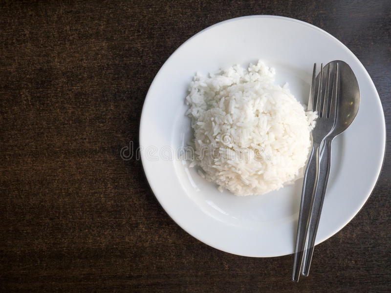 Gekochter Reis in der Schüssel mit Löffel und Geschirrtuch auf altem Holztisch stockfoto