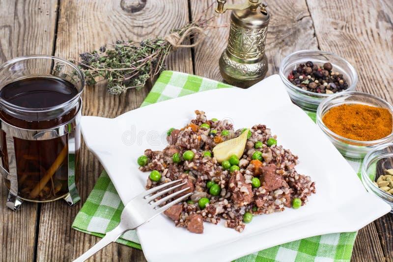 Gekochter roter Reis mit Gemüse und Scheiben des Huhns auf einem woode lizenzfreie stockfotografie