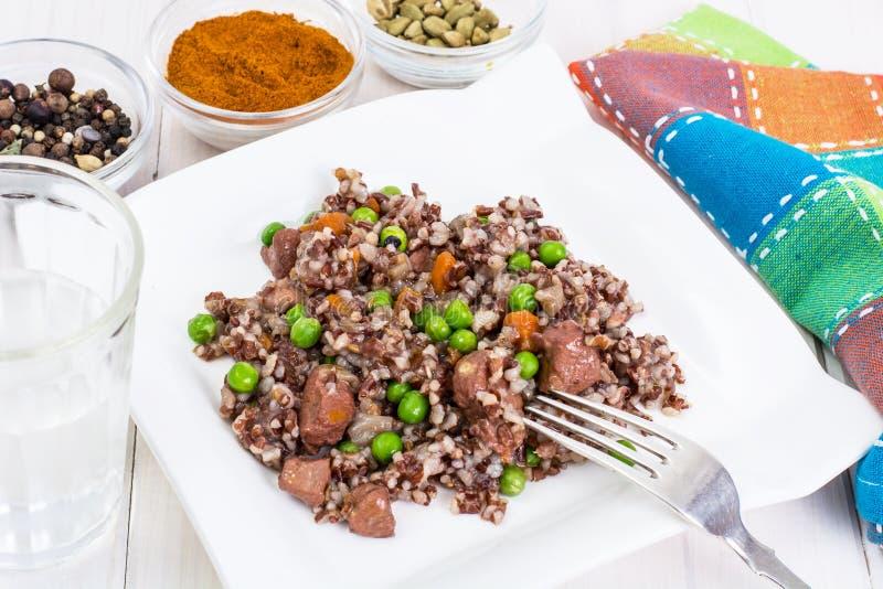 Gekochter roter Reis mit Gemüse und Scheiben des Huhns auf einem woode stockbild