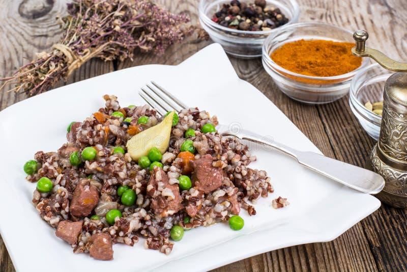 Gekochter roter Reis mit Gemüse und Scheiben des Huhns auf einem woode lizenzfreie stockbilder