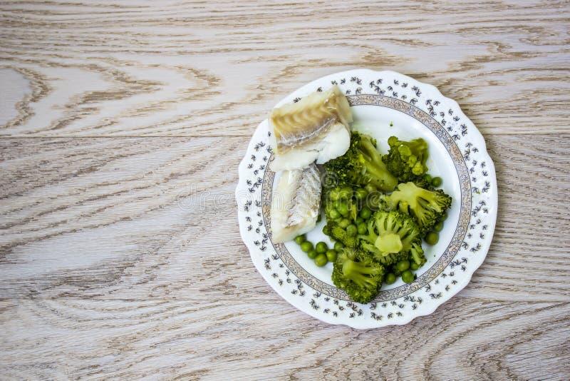 Gekochter Weißfisch, Brokkoli und grüne Erbsen in einer Platte auf einem leeren Holztisch lizenzfreie stockfotos