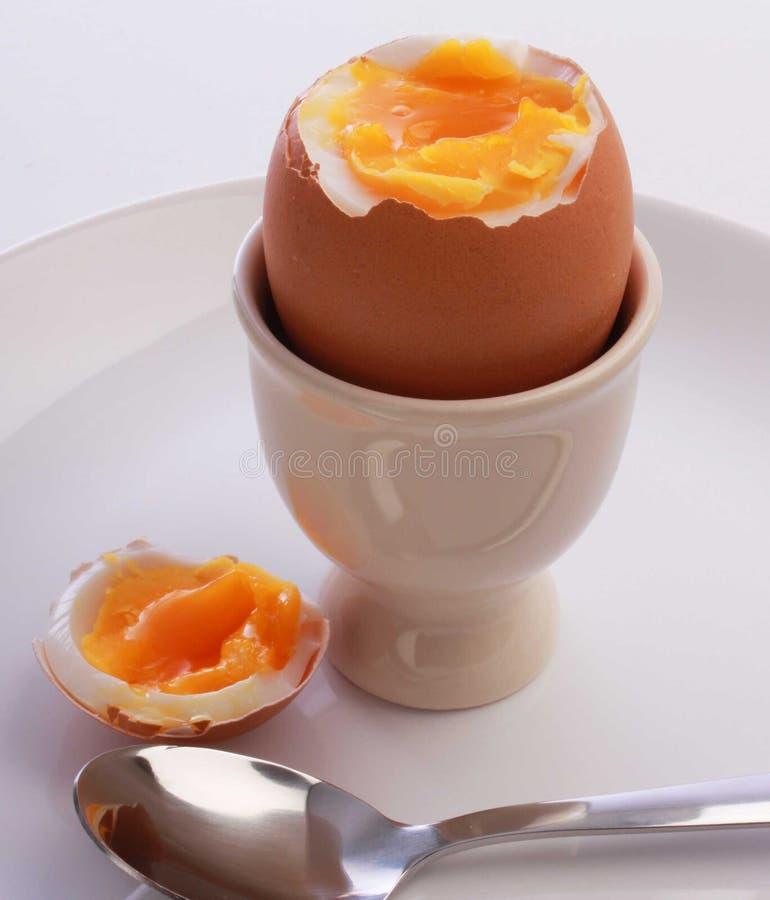 Gekookt ei, besnoeiing open in eierdopje, op plaat met lepel stock foto