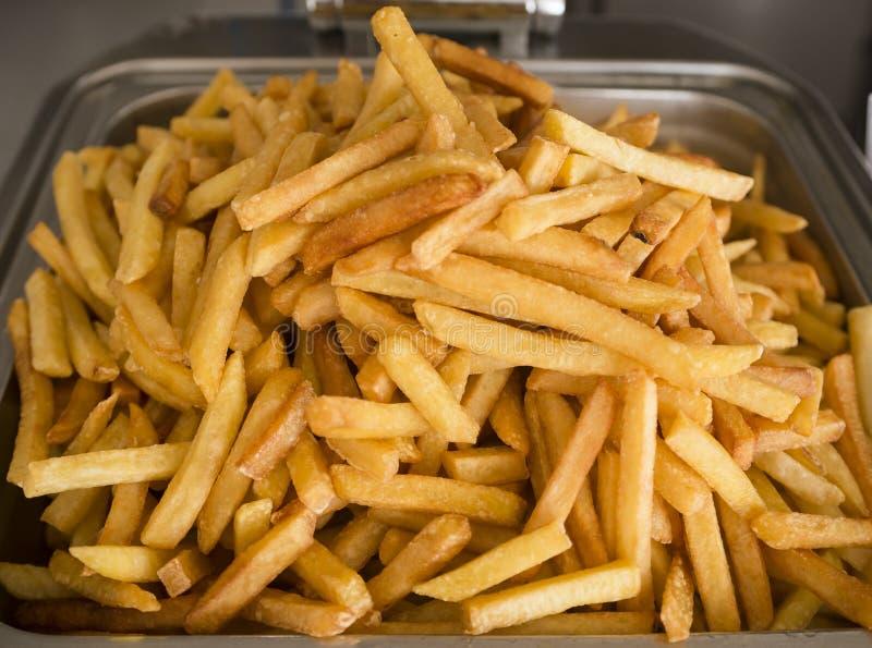 Gekookt frieten vers Restaurantfrituurpan, metaalcontainer met veel gebraden aardappels Straatvoedsel, snel voedsel stock foto