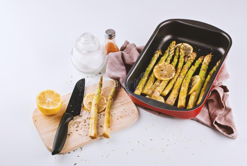 Gekookte asperge in bakseldienblad met citroenplakken en kruiden op witte achtergrond stock fotografie