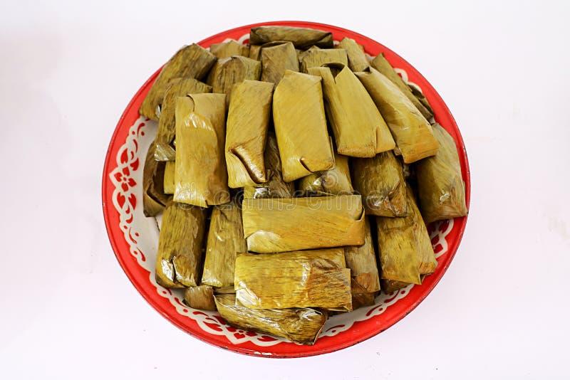 Gekookte die maïsmeelpap in banaanbladeren wordt gevuld met witte achtergrond stock afbeelding