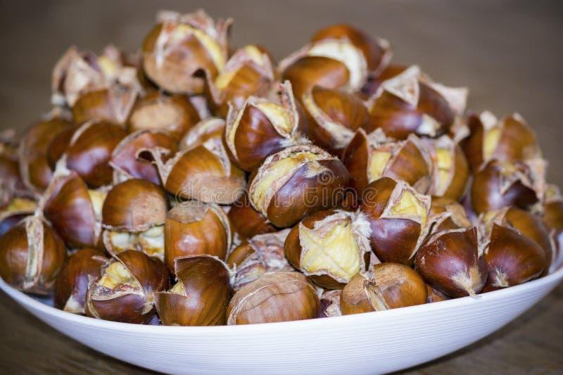 Gekookte eetbare kastanjes op een plaat stock fotografie