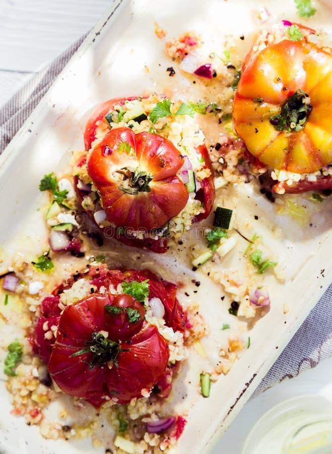 Gekookte gebakken tomaten met verse kruiden stock afbeeldingen