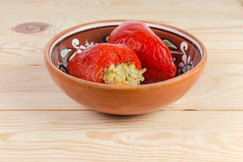 Gekookte gevulde rode groene paprika's in de kleikom stock foto's