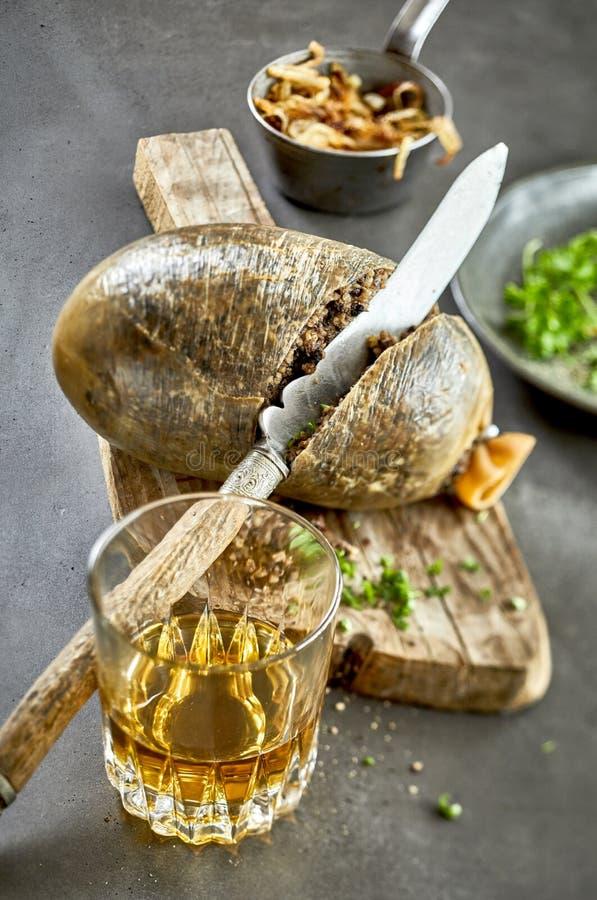 Gekookte haggis met een glas Schotse whisky royalty-vrije stock foto's