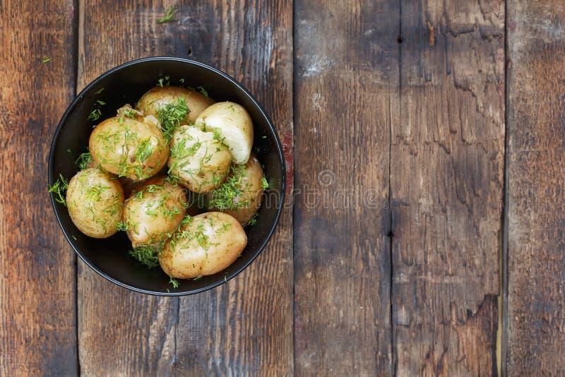 Gekookte jonge aardappels met dille en boter op een houten lijst, hoogste mening, close-up Rustieke stijl royalty-vrije stock foto